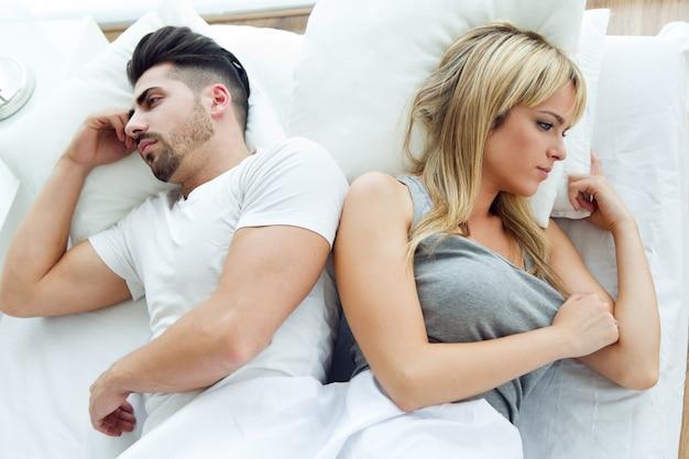 Uśmiechnięta para leży na plecy w łóżku