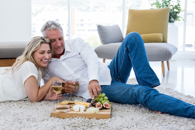 Uśmiechnięta para ma jedzenie podczas gdy kłamający na dywaniku