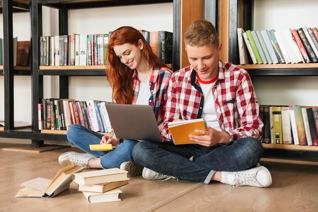 Uśmiechnięta para nastolatków siedzi na podłodze na półce z książkami