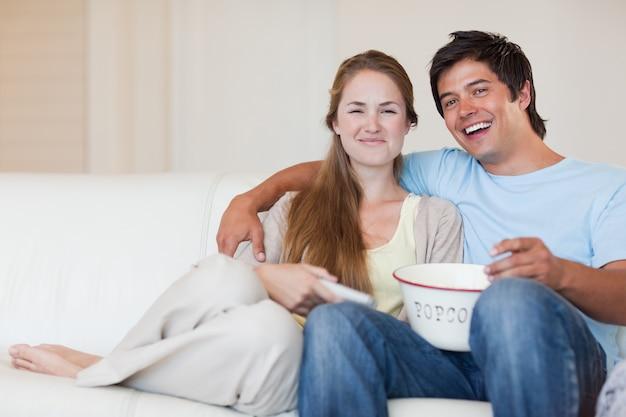 Uśmiechnięta para ogląda telewizję podczas gdy jedzący popkorn