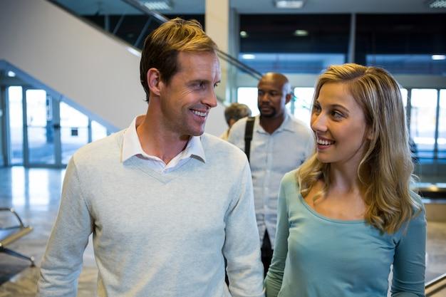 Uśmiechnięta para patrząc na siebie stojąc w poczekalni