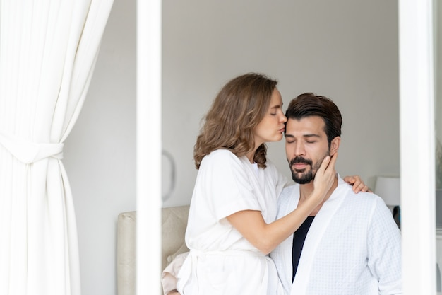 Uśmiechnięta para relaks i pary przytulanie i całowanie w czoło na łóżku