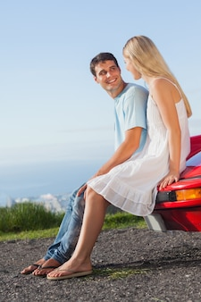 Uśmiechnięta para siedzi na ich cabrio samochód kaptur
