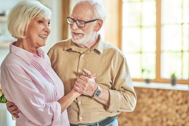 Uśmiechnięta para starszych, ciesząca się czasem spędzonym razem w swoim domu