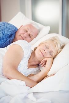 Uśmiechnięta para starszych spanie