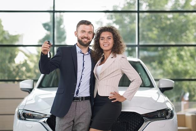 Uśmiechnięta para stoi blisko białego samochodu, patrzeje kamerę.