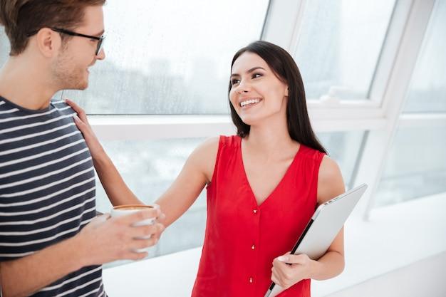 Uśmiechnięta para stojąca przy oknie w biurze. kobieta trzymająca laptopa i dotykająca ramienia mężczyzny trzymającego filiżankę kawy