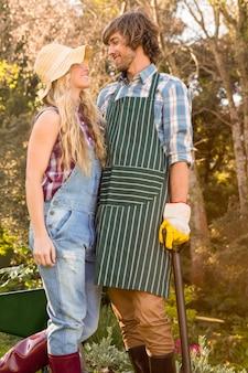 Uśmiechnięta para trzyma łopatę w ogródzie