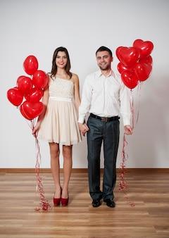 Uśmiechnięta para trzymając się za ręce z balonami