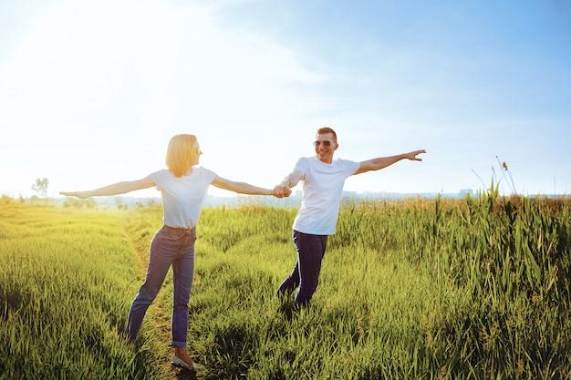 Uśmiechnięta para w białych koszulkach, okularach przeciwsłonecznych i dżinsach rozkłada ramiona