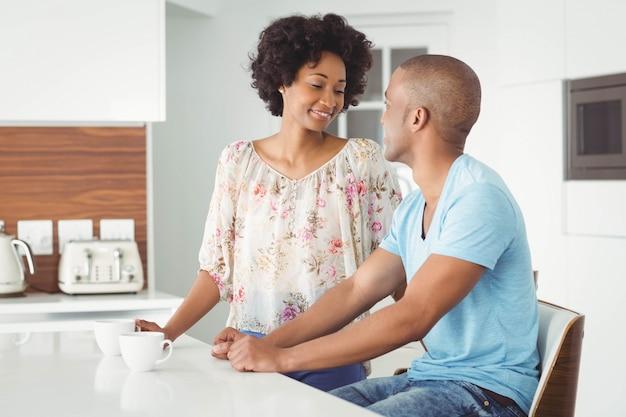 Uśmiechnięta para w kuchni mówi