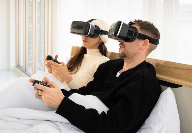 Uśmiechnięta para w łóżku z goglami wirtualnej rzeczywistości i grająca w gry wideo kontrolerem. koncepcja gier i technologii