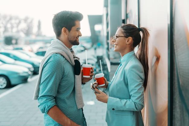 Uśmiechnięta para wielokulturowa ubierała się elegancko stojąc na zewnątrz, patrząc na siebie i pijąc kawę na wynos.