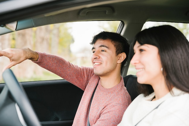 Uśmiechnięta para wskazuje i patrzeje naprzód w samochodzie