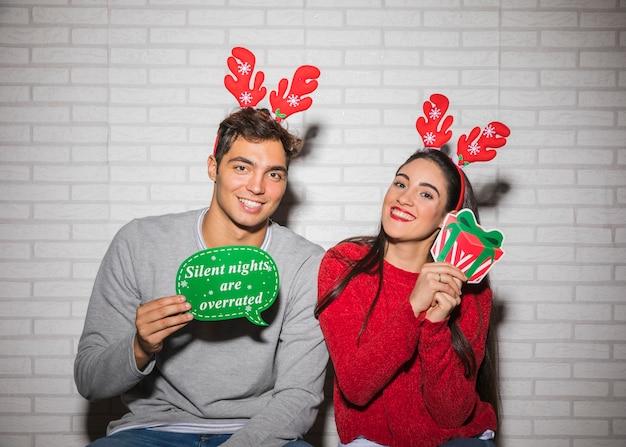 Uśmiechnięta para z bożenarodzeniowymi dekoracjami