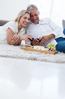Uśmiechnięta para z czerwonym winem i jedzeniem podczas gdy kłamający na dywaniku