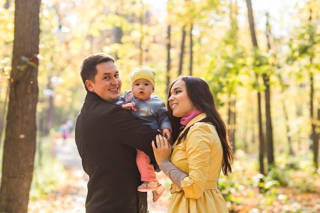 Uśmiechnięta para z dzieckiem w jesień parku
