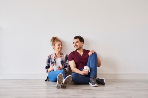 Uśmiechnięta para z kawą robi sobie przerwę od przeprowadzki do domu