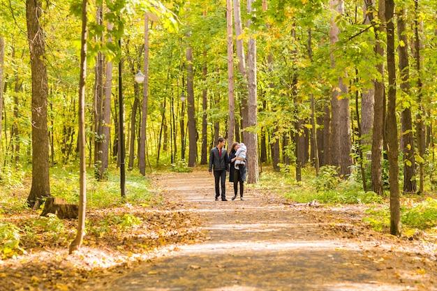 Uśmiechnięta para z nowonarodzonym dzieckiem w parku jesień