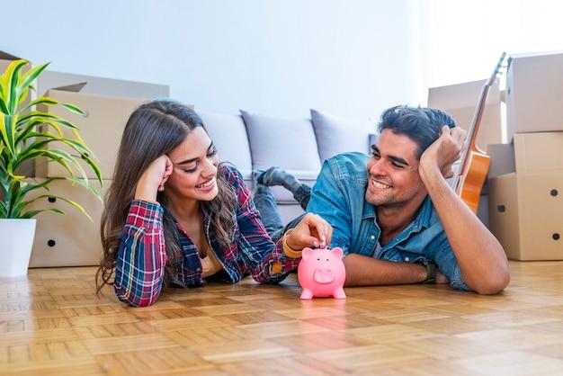 Uśmiechnięta para z piggybank w nowym domu