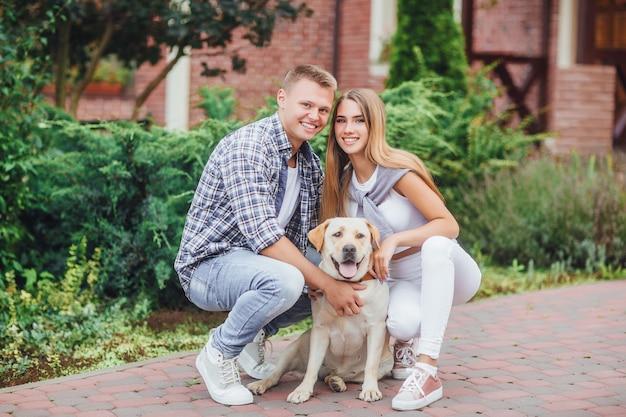 Uśmiechnięta para z psem w parku na słonecznym dniu. piękna młoda rodzina z labradorem.