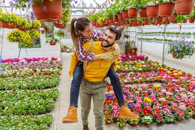 Uśmiechnięta para zakochanych o przejażdżkę na barana w szklarni. wokół nich są kolorowe kwiaty. właściciele małych firm.