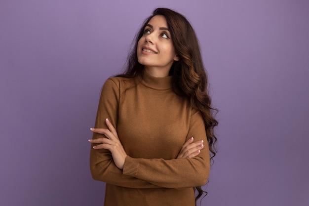 Uśmiechnięta patrząc na bok młoda piękna dziewczyna ubrana w brązowy sweter z golfem, krzyżująca ręce izolowane na fioletowej ścianie