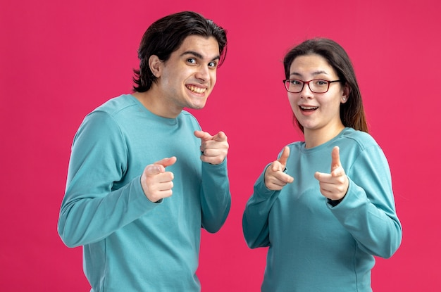 Uśmiechnięta, patrząc na kamerę młoda para na walentynki pokazująca gest odizolowany na różowym tle