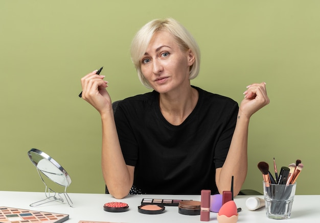Uśmiechnięta, patrząc na kamerę, młoda piękna dziewczyna siedzi przy stole z narzędziami do makijażu, trzymając eyeliner na oliwkowym zielonym tle