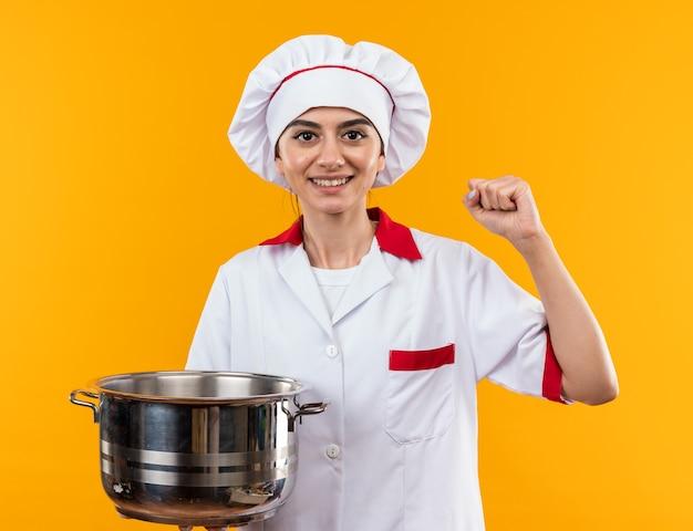 Uśmiechnięta, patrząc na kamerę, młoda piękna dziewczyna w mundurze szefa kuchni trzymająca rondel pokazujący gest