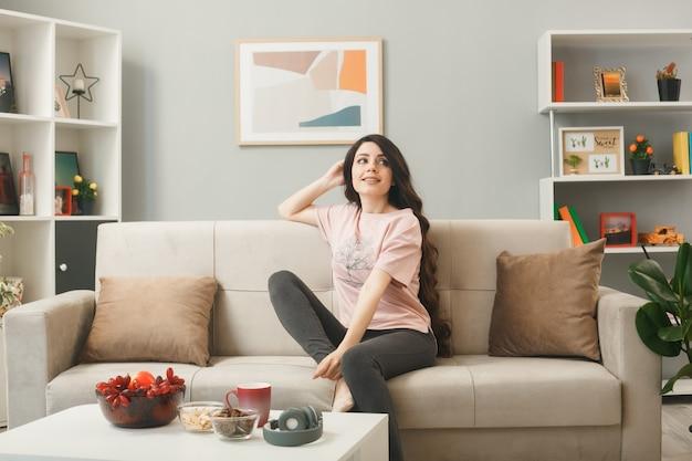 Uśmiechnięta, patrząc z boku, kładąc dłoń na głowie, młoda dziewczyna siedzi na kanapie za stolikiem kawowym w salonie