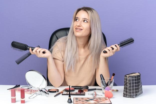 Uśmiechnięta patrząc z boku młoda piękna dziewczyna siedzi przy stole z narzędziami do makijażu trzymając grzebień na białym tle na niebieskim tle