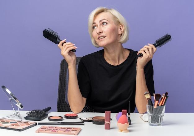 Uśmiechnięta patrząc z boku młoda piękna dziewczyna siedzi przy stole z narzędziami do makijażu, trzymając grzebienie na białym tle na niebieskim tle