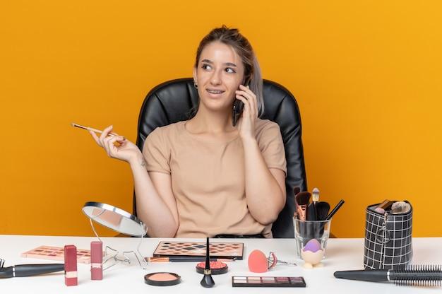 Uśmiechnięta patrząc z boku młoda piękna dziewczyna w aparatach ortodontycznych siedzi przy stole z narzędziami do makijażu, trzymając pędzel do makijażu, mówi na telefonie na białym tle na pomarańczowym tle