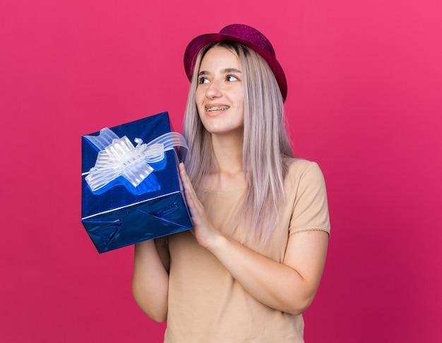 Uśmiechnięta, patrząca w górę młoda piękna dziewczyna w kapeluszu imprezowym, trzymająca pudełko na prezent na różowej ścianie