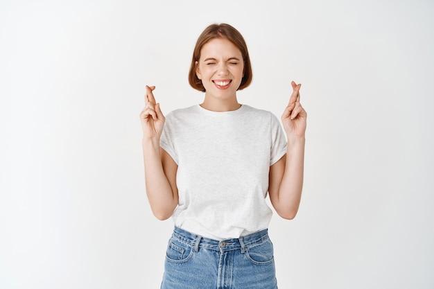 Uśmiechnięta, pełna nadziei dziewczyna zamyka oczy i krzyżuje palce na szczęście, życząc lub modląc się, stojąc w koszulce i dżinsach na białej ścianie
