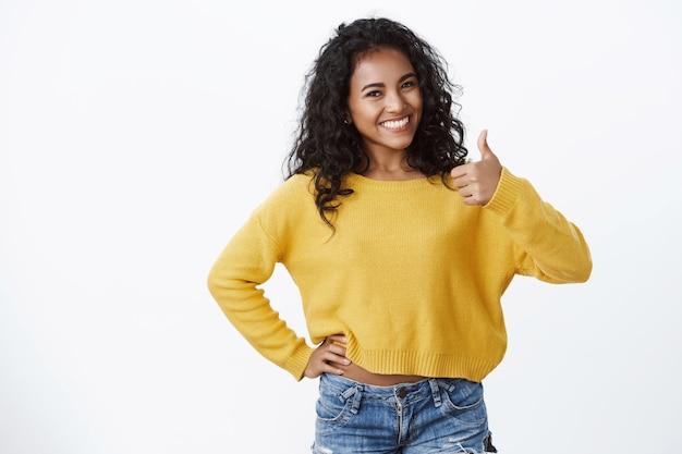 """Uśmiechnięta pewna siebie i pełna energii ładna kobieta nosi żółty sweter, pokazuje kciuk w górę z aprobatą, powiedz """"dobrze zrobione"""", jak koncepcja, biała ściana"""