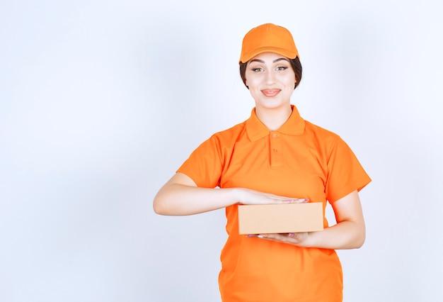 Uśmiechnięta pewna siebie kobieta w unishape trzymającym pakiet na białej ścianie