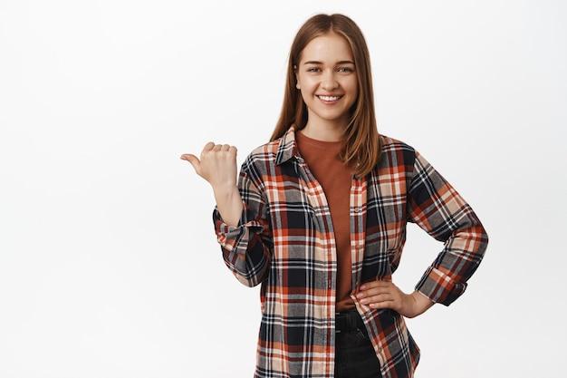 Uśmiechnięta pewna siebie kobieta wskazująca kciukiem w lewo, pokazująca reklamę na bok, ogłaszająca, wskazująca na wykres lub diagram, stojąca w zwykłych ubraniach na białej ścianie