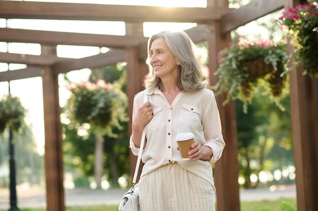 Uśmiechnięta pewna siebie kobieta z torebką i kawą