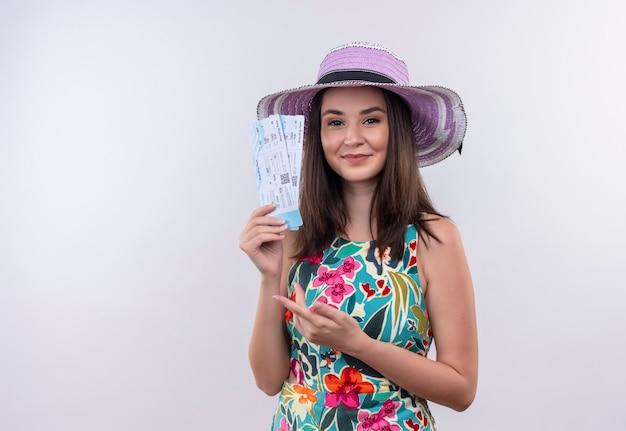 Uśmiechnięta pewna siebie młoda podróżniczka kobieta trzyma bilety lotnicze na na białym tle białej ścianie