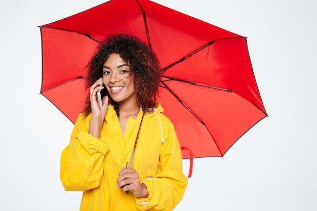 Uśmiechnięta piękna afrykańska kobieta w płaszczu chuje pod parasolem podczas gdy opowiadający smartphone i patrzejący kamerę nad białym tłem