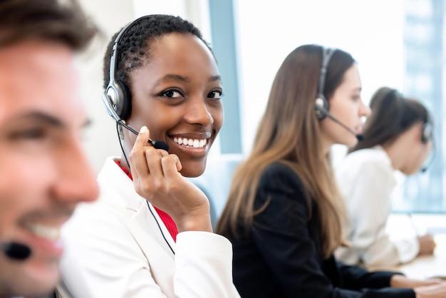 Uśmiechnięta piękna amerykanin afrykańskiego pochodzenia kobieta pracuje w centrum telefonicznym z różnorodną drużyną