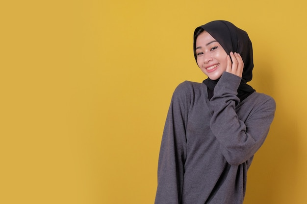 Uśmiechnięta piękna azjatycka dziewczyna jest ubranym casualową koszulkę i czarną zasłonę