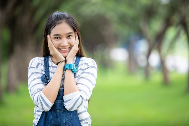 Uśmiechnięta piękna azjatycka dziewczyna przy drzewem na parku w lecie dla relaksuje czas