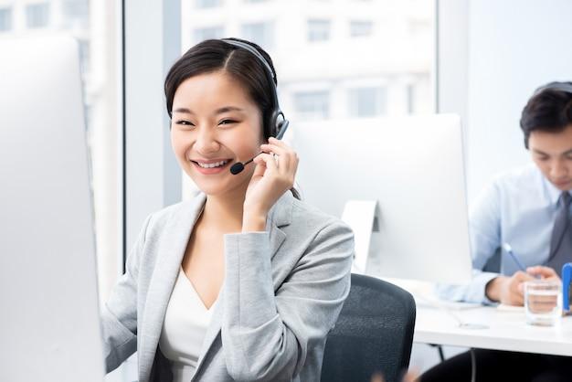 Uśmiechnięta piękna azjatycka kobieta pracuje w centrum telefonicznego biurze jako obsługa klienta operator