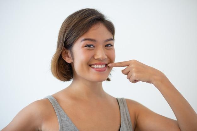 Uśmiechnięta piękna azjatycka kobieta wskazuje przy jej zębami