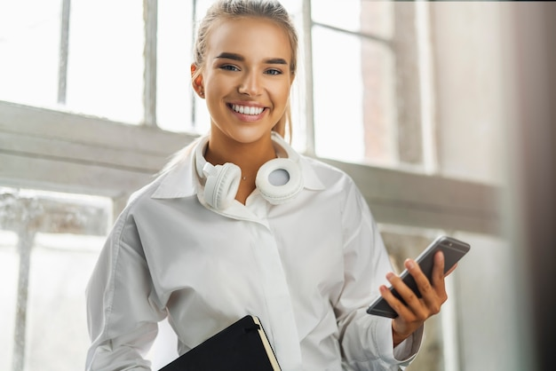 Uśmiechnięta piękna blondynka trzyma w ręku smartfon, czarny notatnik