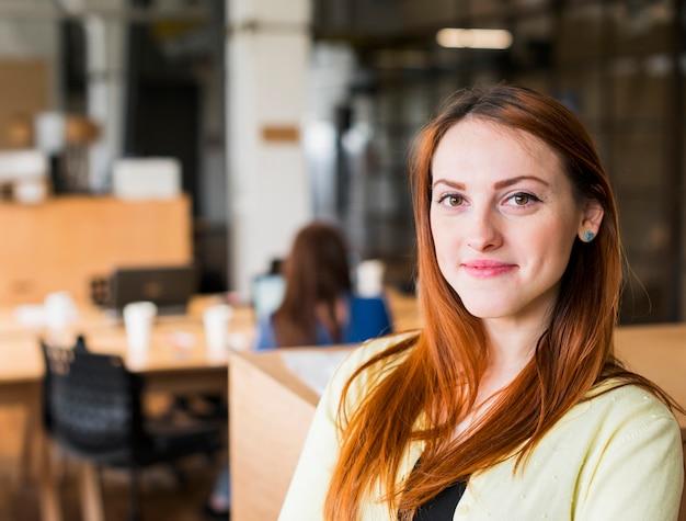 Uśmiechnięta piękna caucasian kobieta w biurowej patrzeje kamerze