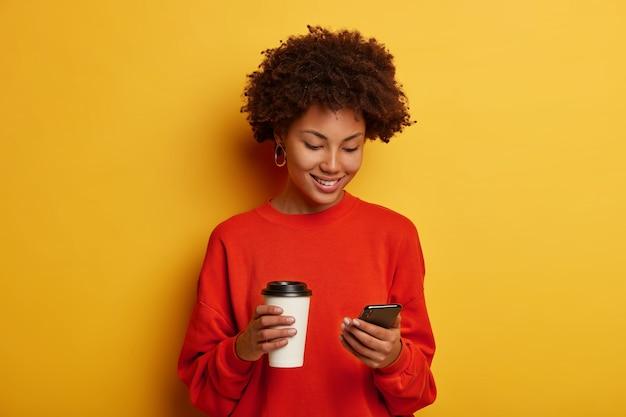 Uśmiechnięta piękna ciemnoskóra kobieta trzyma smartfona